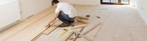 Professionista che effettua la sostituzione di un pavimento in legno su un lavoro di ristrutturazione
