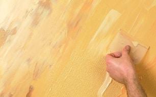 Pittore edile che tinteggia con color giallo