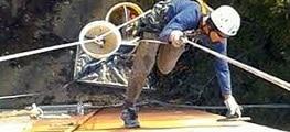 Artigiano che passa il fratazzo su esterno immobile con tecnica dell'edilizia acrobatica