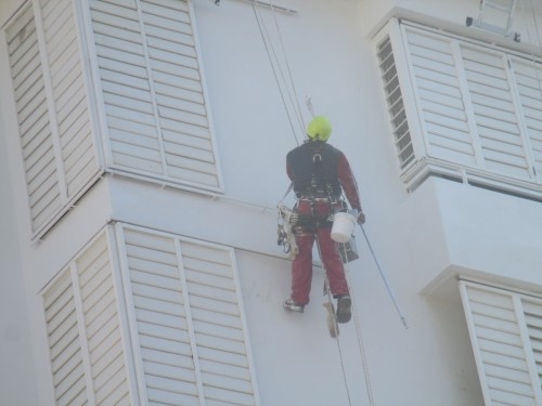 Operaio appeso con la tecnica dell'edilizia acrobatica