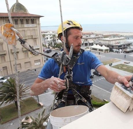 Edilizia acrobatica: operaio attaccato a funi durante il lavoro