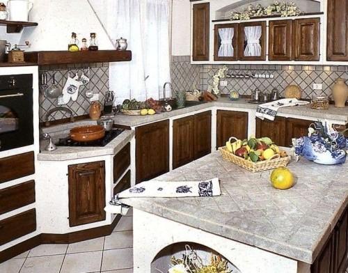 Cucina realizzata in muratura e con sportelli in legno e con isola