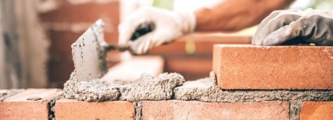 Foto di muratore che mura con malta bastarda