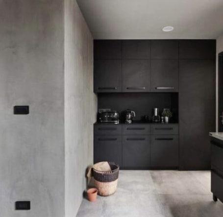 Una cucina con una parete effetto cemento.