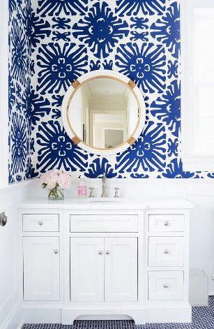 Un bagno con carta da parati di colore azzurro.