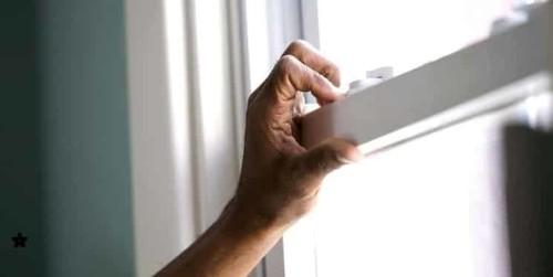Immagine che mostra persona che chiude infisso di casa